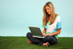 Woman In The Grass With A Computer