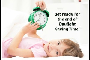 Beautiful little girl with alarm clock on bed in the bedroom